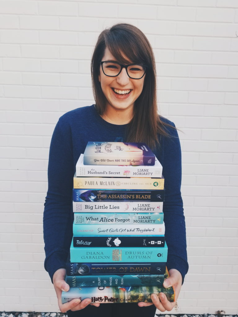 Smiling girl with glasses holding stack of books