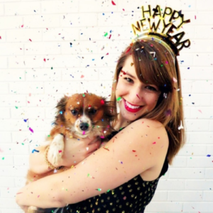 A girl holding a cute dog, wearing a Happy New Year crown with confetti falling down
