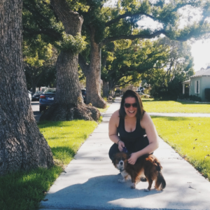 A girl crouched down next to a dog in a neighborhood surrounded by trees