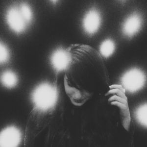 Girl with bright lights behind her, black and white photo