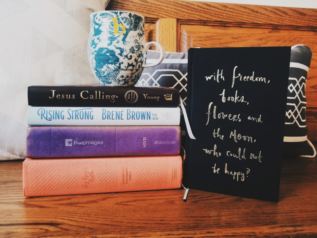 "Stack of books used for my morning quiet time routine with the Lord, with coffee on top and a book standing up right with the quote ""with freedom, books, flowers, and the moon, who could not be happy?"""