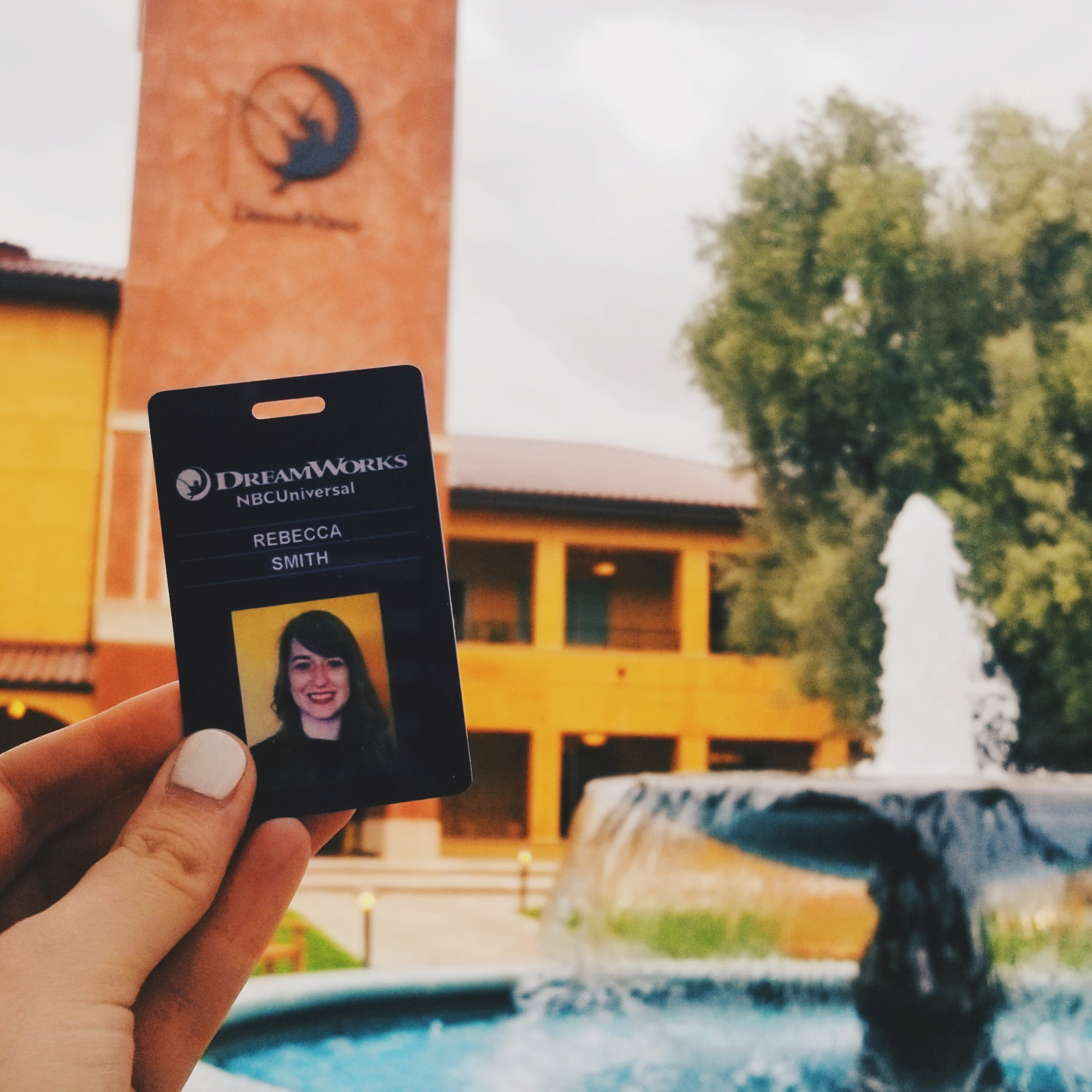 A DreamWorks employee badge in front a fountain and a building that has the DreamWorks logo on it