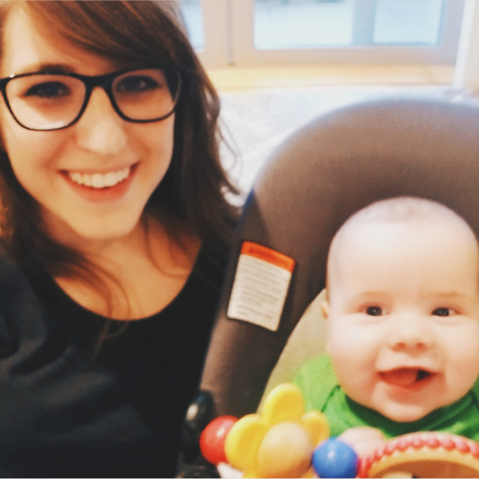 A girl wearing glasses, smiling next to a smiling baby