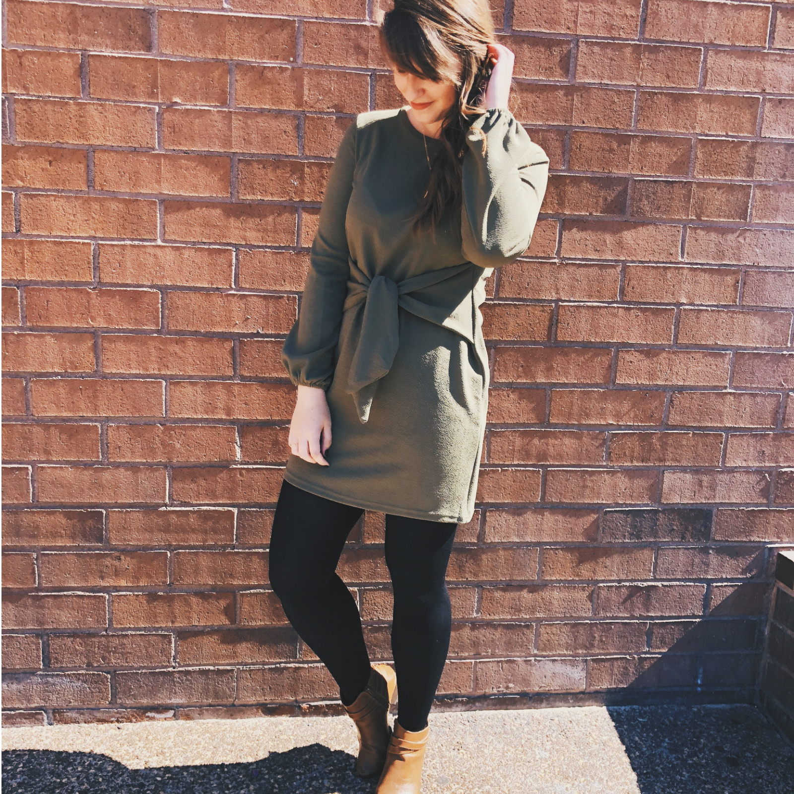 Girl in green dress standing in front of a brick wall