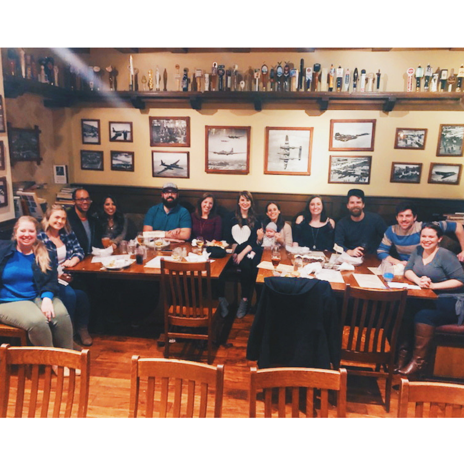 A big group of smiling friends sitting at a table