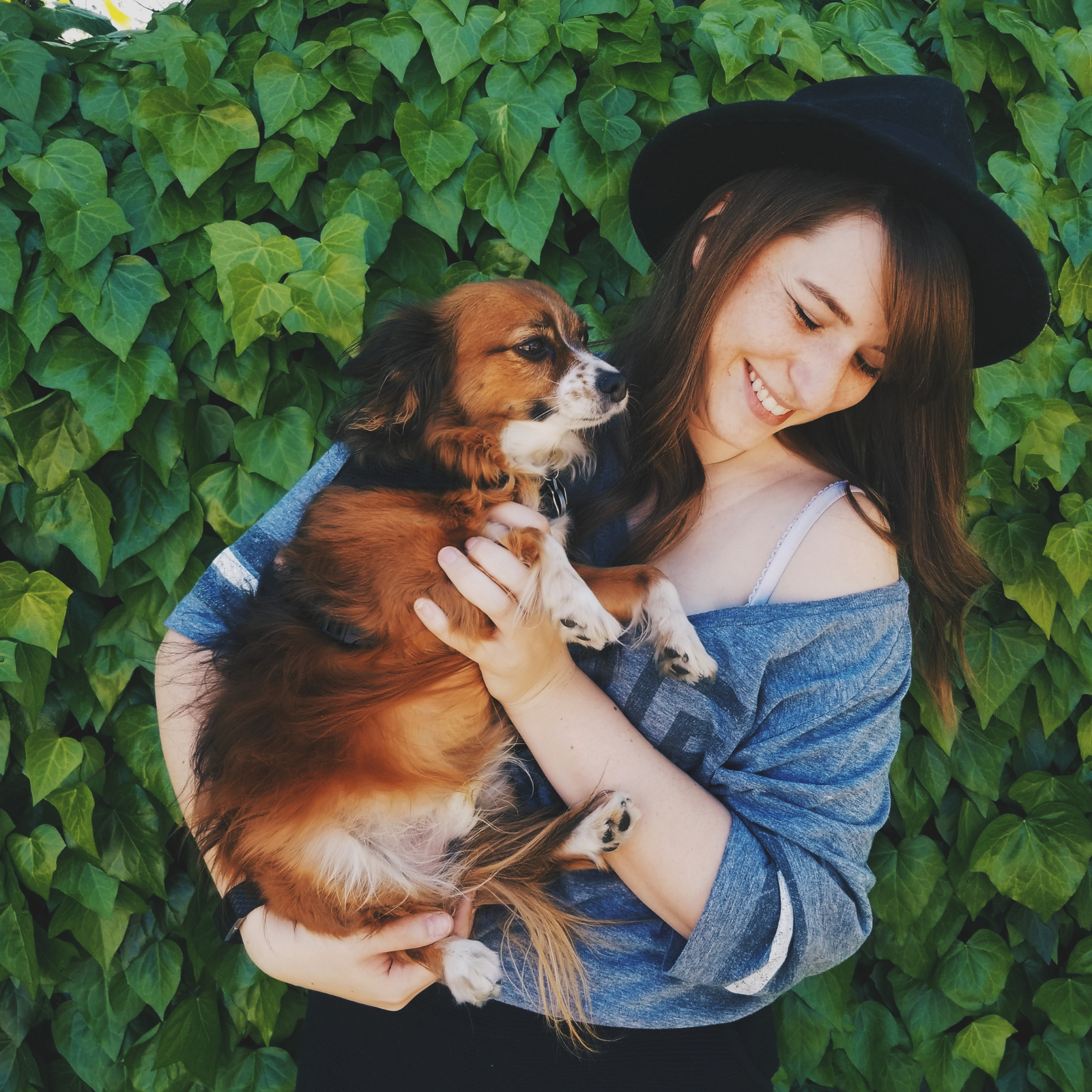 A girl smiling, holding her dog